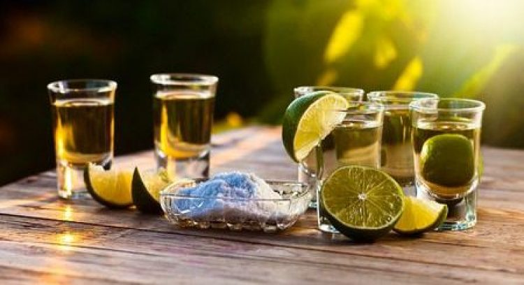 34766347 - gold tequila with salt and lime on old wooden table.